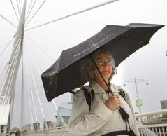 Louise Pallett walks over the Esplanade Riel to work on a rainy Friday morning.