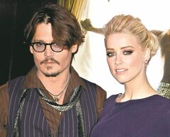 U.S actors Johnny Depp, left, and Amber Heard pose as they arrive for the French Premiere of their movie