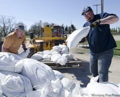 Adrian Van Aert (left) and Kelly Morris help with the loading of pallets of sandbags onto a semi-trailer Sunday morning in Oakville. Oakville received sandbag filling machines Saturday after running out of sandbags with at-risk properties still in need or protection.