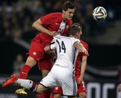 Germany's Oliver Sorg, right, and Poland's Jakub Wawrzyniak, left, challenge for the ball during a friendly soccer match between Germany and Poland in Hamburg, Germany, Tuesday, May 13, 2014. (AP Photo/Michael Sohn)