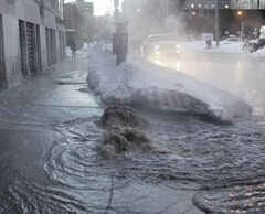 Water gushes from the sidewalk on Bannatyne Avenue between Dagmar and Ellen streets this morning, flooding the area before city crews arrived to start working on it.