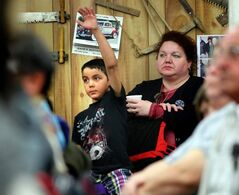 Christian Ali signals his bid while while his mom, Barb Dyck, relaxes behind him.