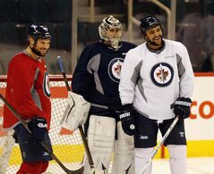 Dustin Byfuglien, right, shares a laugh with teammates as the Winnipeg Jets practise at the MTS Centre Thursday.
