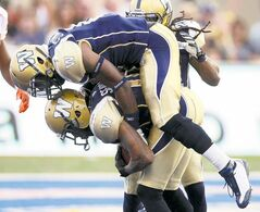 Winnipeg Blue Bombers' DB Johnny Sears (bottom) is congratulated by gleeful teammate Brandon Stewart after Sears picked off a first-quarter pass.