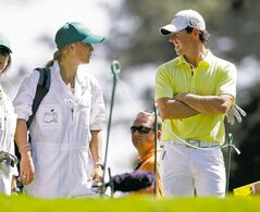 Rory McIlroy chats with his girlfriend and caddy-for-the-day, tennis star Caroline Wozniacki, at the Par 3 Contest. She may have discovered that she should stick to tennis.