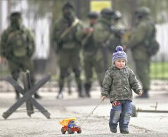 A child drags a toy truck past pro-Russian soldiers standing outside a military base in the Crimea. Ukrainians say all they can do is hope for the best.