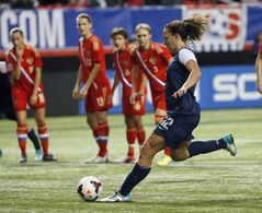 United States' Lauren Holiday (12) scores on a penalty kick in an exhibition soccer match against Russia on Thursday, Feb. 13, 2014, in Atlanta. The United States won 8-0. (AP Photo/John Bazemore)