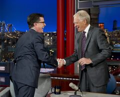 "In this photo provided by CBS, Comedy Central's Stephen Colbert, left, shakes hands with host David Letterman on the set of the ""Late Show with David Letterman,"" Tuesday, April 22, 2014, in New York. The late-night transition from David Letterman to Steven Colbert and from Craig Ferguson to a yet-to-be-named host remains undecided, CBS Entertainment chief Nina Tassler said Thursday, July 17, 2014.Network meetings will be held in August to discuss the scheduling of Colbert's 2015 debut as"