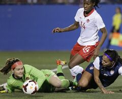 Canada goalkeeper Erin McLeod (1) makes a save as United States forward Sydney Leroux, right, and Kadeisha Buchanan (14) close in during the first half of a soccer game on Friday, Jan. 31, 2014, in Frisco, Texas. (AP Photo/LM Otero)
