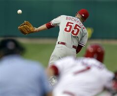 Philadelphia Phillies starting pitcher David Buchanan (55) cannot catch a ball hit back to him by St. Louis Cardinals' Matt Holliday during the first inning of a baseball game, Thursday, June 19, 2014, in St. Louis. Holliday was thrown out at first by Phillies shortstop Jimmy Rollins on the play. (AP Photo/Jeff Roberson)