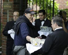 Guests from the New York City Rescue Mission take drinks as they enter The Loeb Boathouse restaurant in New York, Wednesday, June 25, 2014. Recycling magnate Chen Guangbiao, known for his sometimes eccentric gestures served up a fancy lunch Wednesday to hundreds of homeless New Yorkers at a Central Park restaurant and serenaded them with