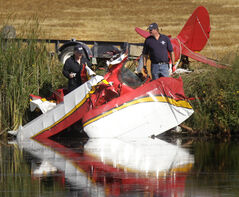 Investigators at the plane wreckage by a lagoon north of the Manitou airstrip Thursday morning. The two occupants of the plane died.