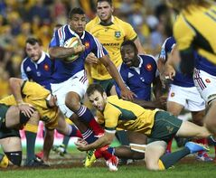 France's Wesley Fofana, left, is tackled by Australia's Nic White during their rugby test match in Brisbane, Australia, Saturday, June 7, 2014. (AP Photo/Tertius Pickard)