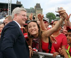 Prime Minister Stephen Harper smiles as has his picture taken with a Canada Day celebrant on Parliament Hill in Ottawa, Tuesday July 1, 2014. THE CANADIAN PRESS/Fred Chartrand