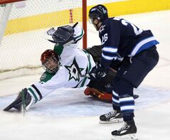 Dallas Stars goaltender Tim Thomas makes a sprawling save against Winnipeg Jets forward Blake Wheeler during first-period NHL action at the MTS Centre in Winnipeg Sunday. The Jets went on to record a 7-2 win.