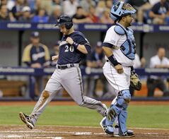 Milwaukee Brewers' Jonathan Lucroy (20) scores past Tampa Bay Rays catcher Jose Molina on an RBI single by Aramis Ramirez off Rays pitcher David Price during the third inning of an interleague baseball game Wednesday, July 30, 2014, in St. Petersburg, Fla. (AP Photo/Chris O'Meara)