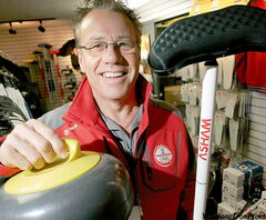 Arnold Asham displays his newest innovation, a curling broom with a brush shaped like a boomerang.