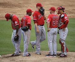 Los Angeles Angels relief pitcher Mike Morin, center, meets with pitching coach Mike Butcher (23) and teammates on the mound during the sixth inning of a baseball game against the Kansas City Royals on Saturday, June 28, 2014, in Kansas City, Mo. (AP Photo/Charlie Riedel)