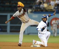 Los Angeles Dodgers' Hanley Ramirez and Arizona Diamondbacks shortstop Didi Gregorius wait for the call from the umpire as Ramirez is called safe on a steal in the sixth inning of a baseball game Saturday, June 14, 2014, in Los Angeles. (AP Photo/Jayne Kamin-Oncea)