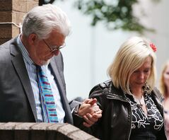 Veteran entertainer Rolf Harris holds the hand of his daughter Bindi, accompanied by other family members, as they leave Southwark Crown Court in London, Monday, June 30, 2014. A jury Monday found Australian-born Harris guilty of 12 counts of indecent assault, convicting the 84-year old of indecent assault on four victims aged 19 or under between 1968 and 1986. Harris denied the charges. (AP Photo/Lefteris Pitarakis)
