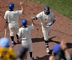 Kansas City Royals' Alex Gordon, right, celebrates coming into the dugout after hitting a three-run home run during the seventh inning of a baseball game against the Baltimore Orioles, Sunday, May 18, 2014, in Kansas City, Mo. It was Gordon's second three-run home run in the game. (AP Photo/Charlie Riedel)