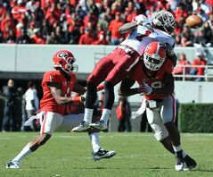 Georgia defenders Branden Smith, left, and Bacarri Rambo break up a pass intended for  New Mexico State's Taveon Rogers during the first half of a game in Athens, Georgia, in November 2011.