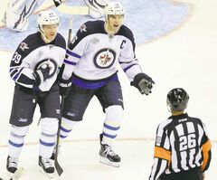 Jets blue-liner Tobias Enstrom (39) and captain Andrew Ladd protest a slashing penalty on Enstrom by referee Rob Martell Thursday night.