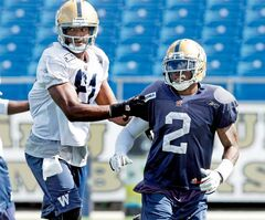 Receiver Cory Watson grabs hold of newest Bombers strong-side linebacker Jovon Johnson, who is making the switch from cornerback for the Banjo Bowl on Sunday.