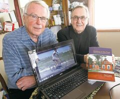 Alvin Suderman (left) and author Rudy Friesen with a laptop displaying a photo of a boy who lost both arms and rides a special bike built for him by the Mennonite Centre in the Ukrainian farm town of Molochansk.