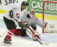 Team Canada goaltender Jake Paterson makes a save on forward Kerby Rychel during team practice at the IIHF World Junior Hockey Championships in Malmo, Sweden on Wednesday December 25, 2013. THE CANADIAN PRESS/ Frank Gunn