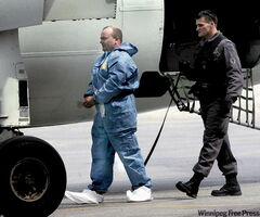 Michael Sandham is led away in shackles by an OPP officer to a plane waiting to transport him from Winnipeg to Ontario to face charges.
