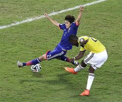 Colombia forward Jackson Martinez, right, scores past Japan defender Atsuto Uchida during the second half of a group C World Cup soccer match at the Arena Pantanal in Cuiaba, Brazil, Tuesday, June 24, 2014. (AP Photo/Shuji Kajiyama)
