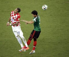 Croatia's Mario Mandzukic and Mexico's Hector Moreno challenge for the ball during the group A World Cup soccer match between Croatia and Mexico at the Arena Pernambuco in Recife, Brazil, Monday, June 23, 2014. (AP Photo/Hassan Ammar)