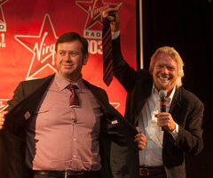 Sir Richard Branson, Chairman of Virgin Group, holds up the end of a tie he cut from Rob Farina, Executive Vice President of Content at Astral Radio, during Branson's Winnipeg Chamber of Commerce Q&A at the Fairmont Hotel on Friday.  The luncheon and an auction for a week at Sir Richard's private island helped raise over $300,000 for Resource Assistance for Youth (RaY).