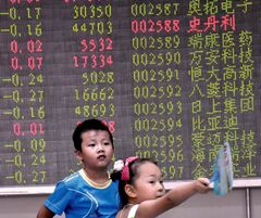 Children play in front of a screen showing the China Composite Stock Price Index. China's GDP is expected to soften this year.