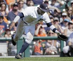Detroit Tigers left fielder Rajai Davis drops a fly ball hit down the left field line by Seattle Mariners' Kendrys Morales during the sixth inning of a baseball game Sunday, Aug. 17, 2014, in Detroit. Davis was given an error on the play and Seattle Mariners' Austin Jackson scored from third base. (AP Photo/Duane Burleson)