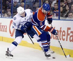 Tampa Bay Lightning Ondrej Palat (18) and Edmonton Oilers Jeff Petry (2) battle for the puck during first period NHL hockey action in Edmonton, Alta., on Sunday January 5, 2014. The Oilers have agreed to terms with defenceman Petry on a one-year contract. THE CANADIAN PRESS/Jason Franson