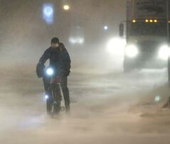 An all-weather cyclist waits for traffic lights to change while the snow swirls around at the corner of Portage Avenue and Fort Street Friday morning.