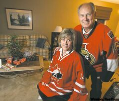 Rob and Jackie Stone get into the hockey mood in their St. James  living room. The couple's son Mark is playing in the world junior championship.