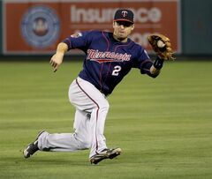 Minnesota Twins second baseman Brian Dozier stops a grounder by Los Angeles Angels' Kole Calhoun during the fourth inning of a baseball game in Anaheim, Calif., Wednesday, June 25, 2014. Calhoun was out at first. (AP Photo/Chris Carlson)