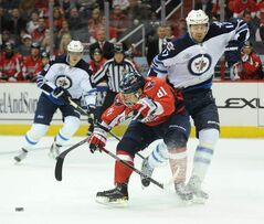 Winnipeg Jets' right-winger Eric Fehr (17) gets knocked off the puck by Washington Capitals defenceman Dmitry Orlov (81) during first-period action in Washington, D.C., Thursday.