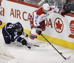 Winnipeg Jets forward Bryan Little dives for the puck as Washington Capitals defenceman Karl Alzner gains control.