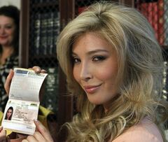 FILE - In this April 3, 2012, file photo, Jenna Talackova, who advanced to the finals of the Miss Canada competition, part of the Miss Universe contest, shows her passport that lists her gender as female, during a news conference in Los Angeles. Talackova says she was forced out of the competition because Pageant officials alleged she was not