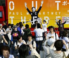 Fans take photos of themselves in front of a tour truck bearing an image of Paul McCartney after his concert was cancelled at Natinal Stadium, the site of his concert in Tokyo, Sunday, May 18, 2014. McCartney has canceled his second concert in Japan, as well as the makeup performance for the one nixed a day earlier, and apologized to his fans for still being sick with a virus. The former Beatle said on his