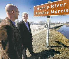 Premier Greg Selinger (right) and Morris Mayor Gavin van der Linde survey the rising river level.