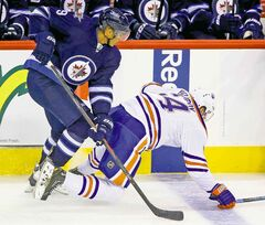 The Jets' Evander Kane (9) takes down the Oilers' Nail Yakupov (64) during their pre-season game at the MTS Centre Winnipeg Tuesday.