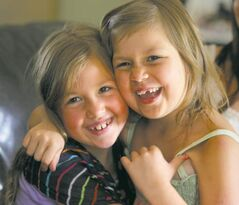 Six-year-old Sophia Penner (right) gets a loving hug from big sister Alexis, 7. Sophia has been doing remarkably well since her last treatment for leukemia.