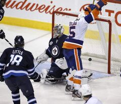 New York Islanders' PA Parenteau (15) scores past Winnipeg Jets goaltender Ondrej Pavelec (31) Winnipeg, Tuesday. The Jets hit the road to play Minnesota, another team struggling to win games recently.