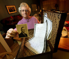 Thelma Unruh displays a photo of her father with the little brown suitcase he arrived in Canada with in 1910 as an 11-year-old.