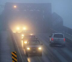 Traffic rolls over the Arlington Bridge through ice fog Monday morning.